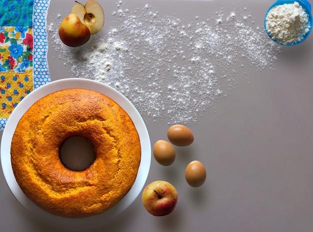 식탁에 있는 사과 케이크에는 천, 계란, 밀가루, 사과가 요리용으로 들어 있습니다.