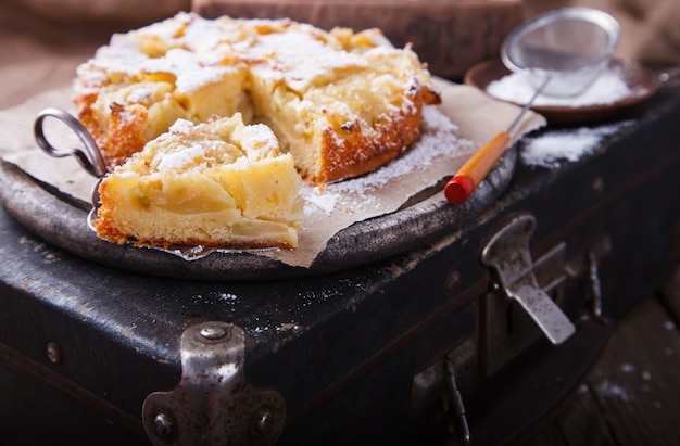 Apple cake on a vintage suitcase in powdered sugar.