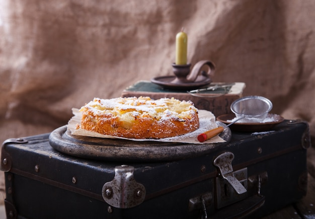 Apple cake on a vintage suitcase in powdered sugar