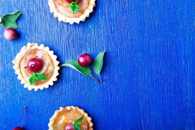 Apple caramel little tarts on blue rustic surface