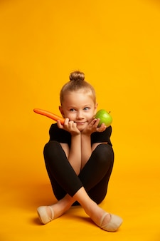 An apple, carrot and sports girl on a yellow background. dieting and healthy eating concept