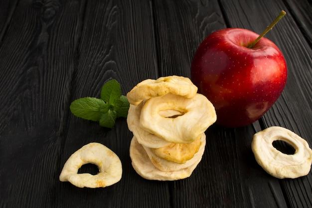 黒い木製のリンゴチップと赤いリンゴ