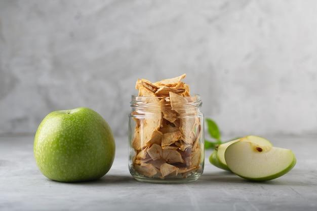 瓶にリンゴのチップとテーブルの上のこの果物の破片