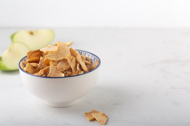 白いボウルのアップルチップとテーブルの上のこの果物のかけら