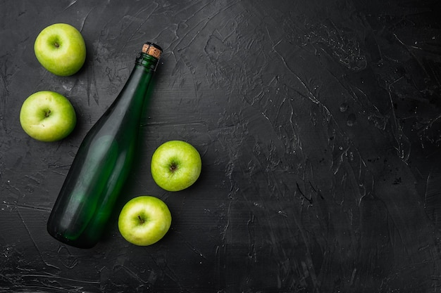 Apple cider bottle set, on black dark stone table background, top view flat lay, with copy space for text