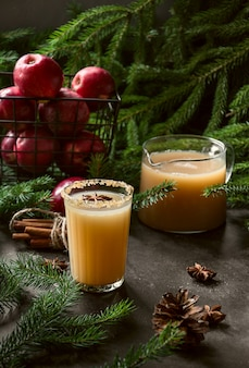 Apple cider cocktail with cardamon and star anise on black table with fir tree branches.