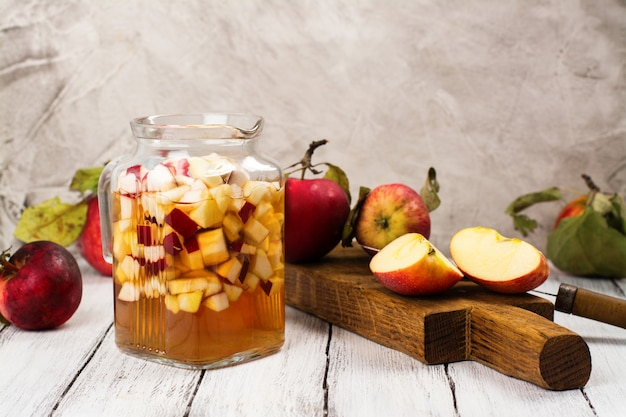 Apple cider sangria in a glass jar on wooden table