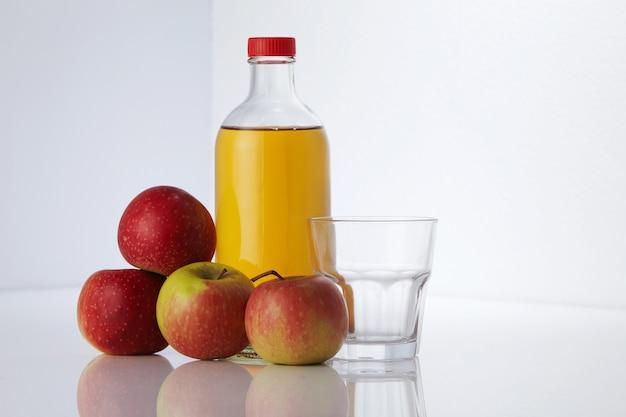 白い表面にリンゴ酢と新鮮なリンゴ