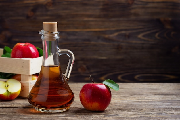 Apple cider vinegar and fresh red apple on a wooden background