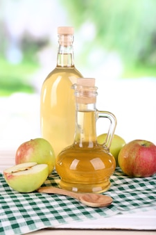 Apple cider vinegar in glass bottles and ripe fresh apples, on wooden table, on nature background