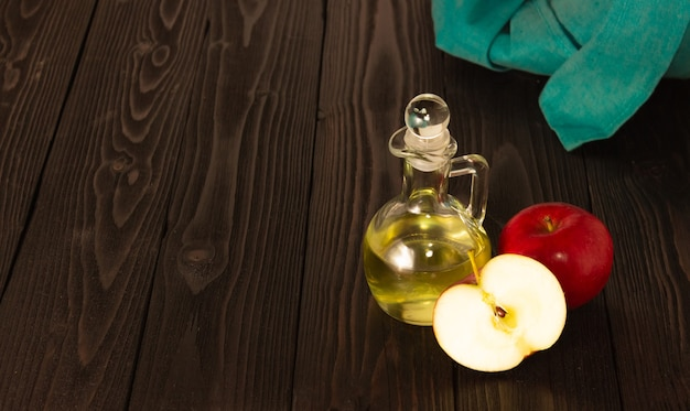 Apple cider vinegar in a glass decanter on a dark wooden table