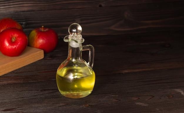 暗い木製のテーブルの上のガラスデカンターのアップルサイダー酢