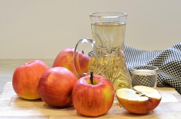 유리 병에 사과 사과 식초와 나무 배경에 신선한 사과.