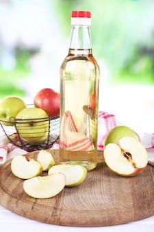 ガラス瓶と熟した新鮮なリンゴのリンゴ酢、木製のテーブル、自然空間