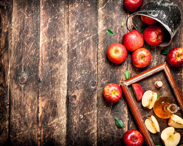 Apple cider vinegar, red apples in the old tray . on wooden table.