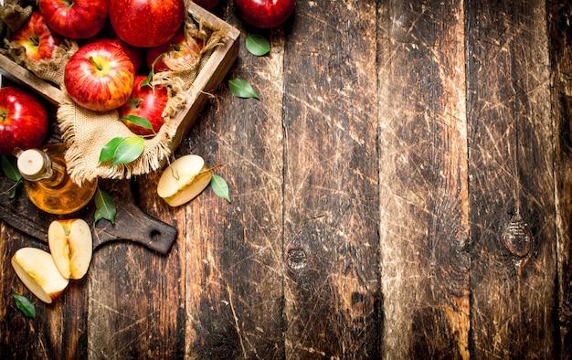Яблочный уксус, красные яблоки на деревянном столе.