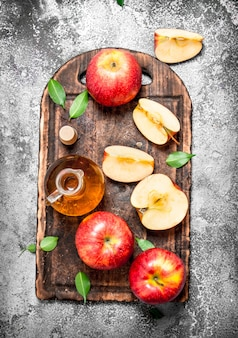 Apple cider vinegar with fresh apples on cutting board