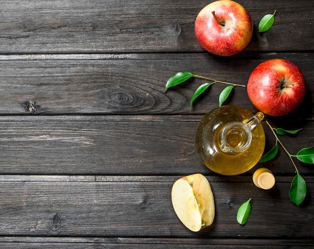 Яблочный уксус со свежими яблоками. на деревянном.