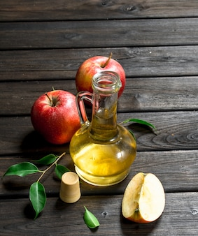 Apple cider vinegar with fresh apples. on wooden surface.