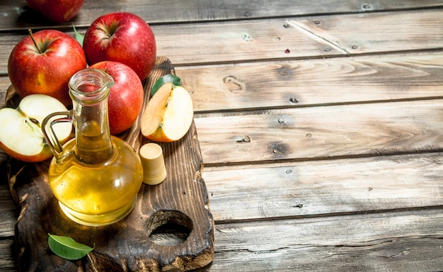 Apple cider vinegar with fresh red apples on a cutting board. on grey wooden background.