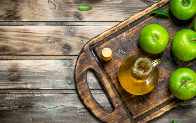 Apple cider vinegar with green apples on an old board.