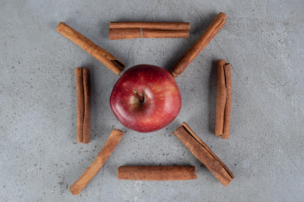 An apple and cinnamon cuts decoratively arranged on marble surface