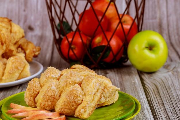 テーブルの上のバスケットに新鮮な赤と緑のリンゴとリンゴシナモンシュトルーデル