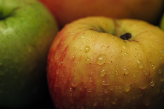 Apple close up with small water droplets on the peel