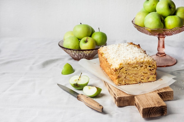 Apple and coconut oaf cake on wooden cutting board and apples in a vase. copy space