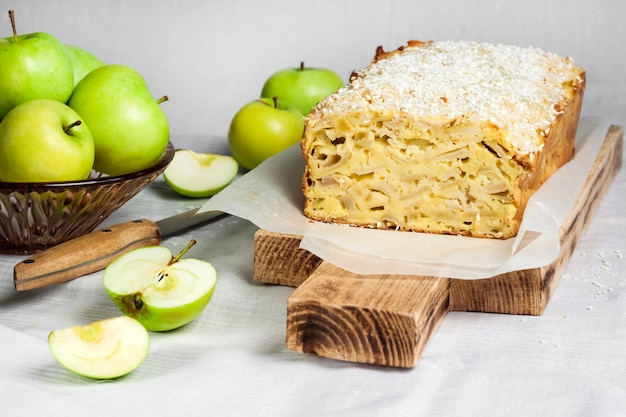 Apple and coconut oaf cake on wooden cutting board and apples in a vase