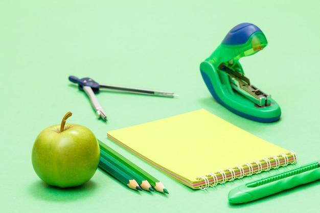Яблоко, цветные карандаши, компас, блокнот, нож для бумаги и степлер на зеленом фоне. снова в школу концепции. школьные принадлежности. малая глубина резкости.