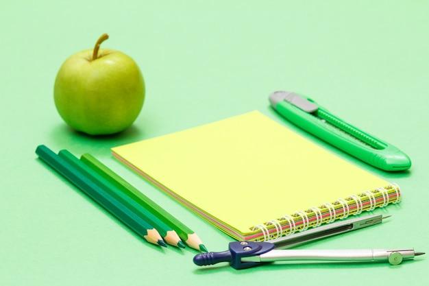 Яблоко, цветные карандаши, блокнот, компас и нож для бумаги на зеленом фоне. снова в школу концепции. школьные принадлежности. малая глубина резкости.