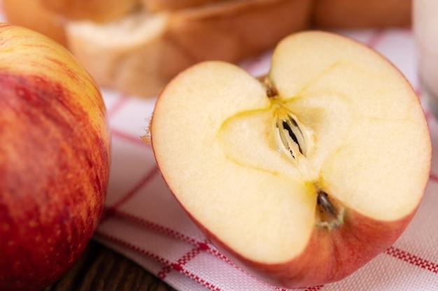 リンゴは木製のテーブルの上に置かれた赤白い布で半分にカットされました