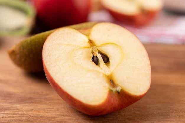 リンゴは木製のテーブルで半分にカット