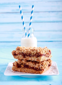 Apple and date bars on plate and milk in a bottle