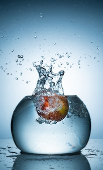 An apple dropped into fish bowl with too much water splash
