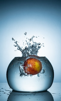 An apple dropped into fish bowl with water splash