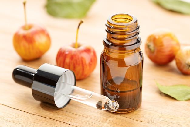 木製のテーブルにアップルのエッセンシャルオイルのボトルとピペット。アップルオイル