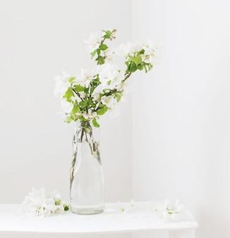 Яблочные цветы в стеклянной вазе в белом интерьере