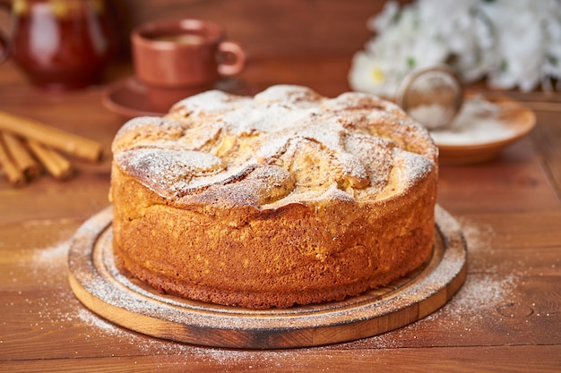 Apple french cake with apples, cinnamon on dark wooden kitchen table