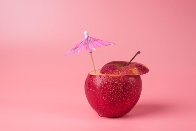 アップルの新鮮なコンセプト。ピンクの背景に分離されたカクテル傘とカットリンゴのクローズアップ写真