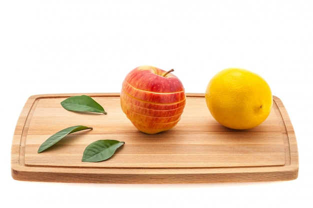 Apple fresh and juicy with green leaves and lemon on a cutting board made of wood.