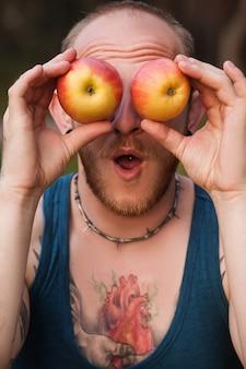 健康的な概念を冗談を言っているリンゴの果実の自然の入れ墨の男。適切な栄養の宣伝。ヘルスケアのライフスタイル。