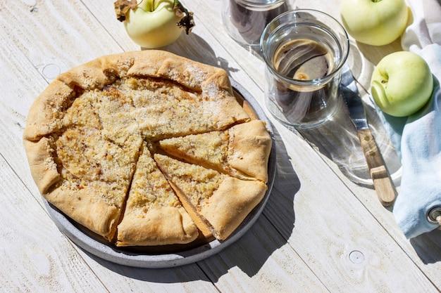 Яблочный галет с штрейзелем из фундука, подается с кофе на деревянном фоне. деревенский стиль.