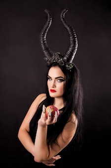 An apple in the hands of a horned witch