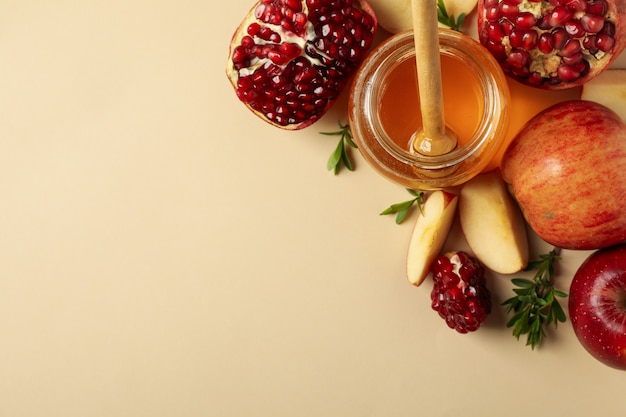 Яблоко, мед и гранат на бежевом, вид сверху. домашнее лечение