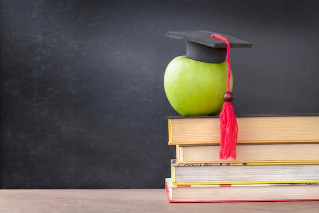 Apple в кепке выпускника на книгах