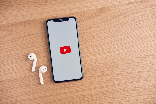 Apple iphoneのテーブル上のyoutube画面、youtubeは人気のあるオンラインビデオ共有webサイトです。