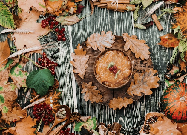 Apple jam and autumn leaves on old wooden table background