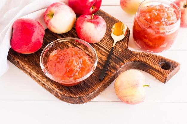 Яблочное варенье в стеклянной банке и миске на деревянной доске.